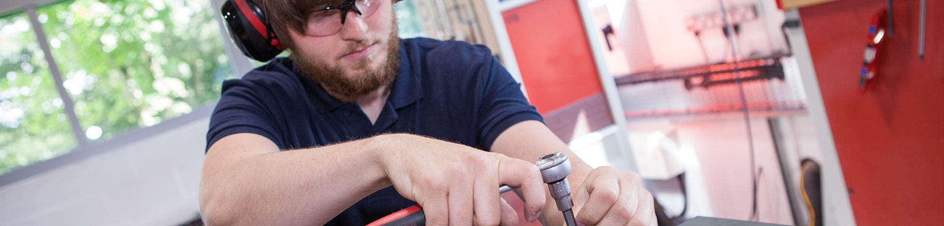 A technician working on an electrodynamic generator (shaker)