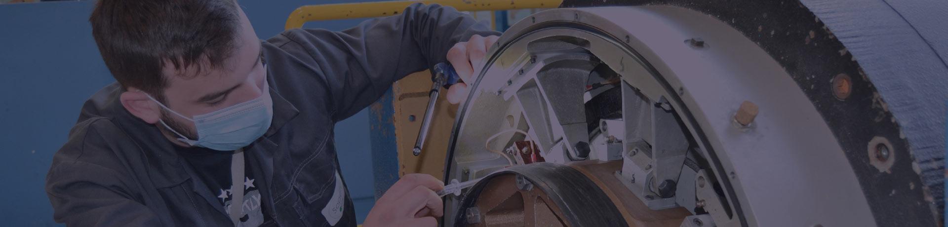 A man performs a maintenance operation on an equipment