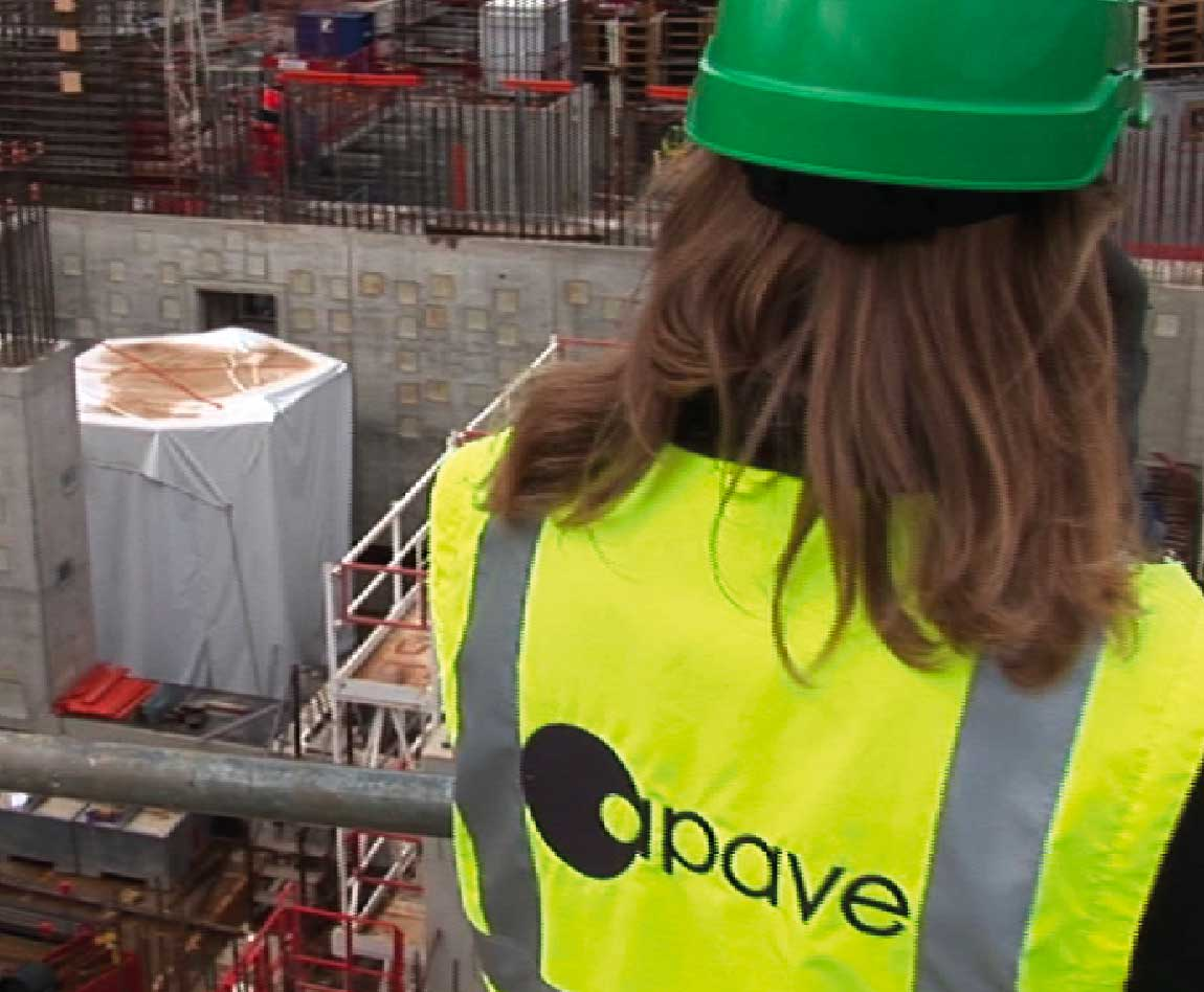 A woman wearing an Apave safety vest and helmet on a construction site