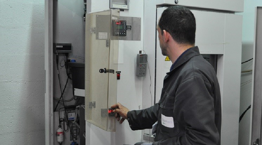 A maintenance technician working on a climatic chamber