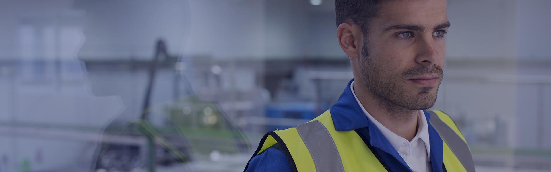 Un homme regarde vers la droite. Il porte un bleu de travail et un gilet jaune.