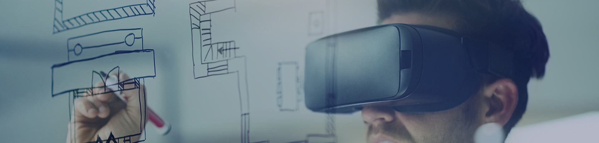 A man with a virtual reality headset writing on a board