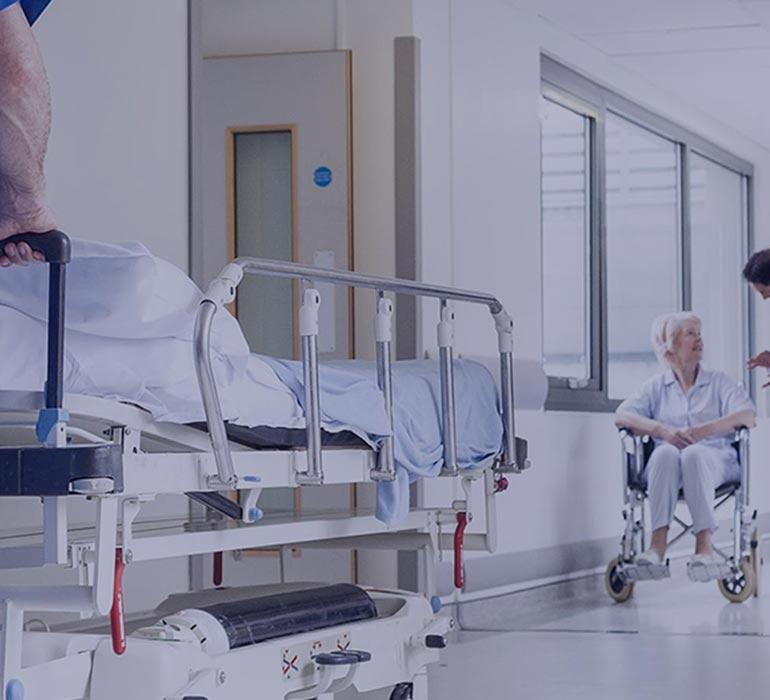 Dans un couloir d'hôpital, un homme pousse un lit médical