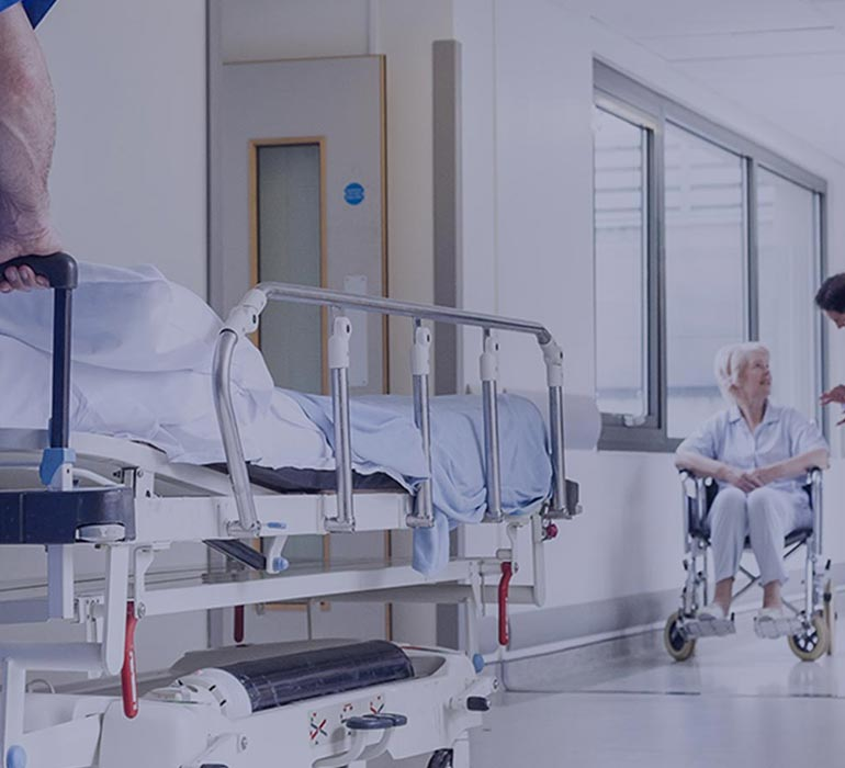 In a hospital corridor, a man pushes a medical bed