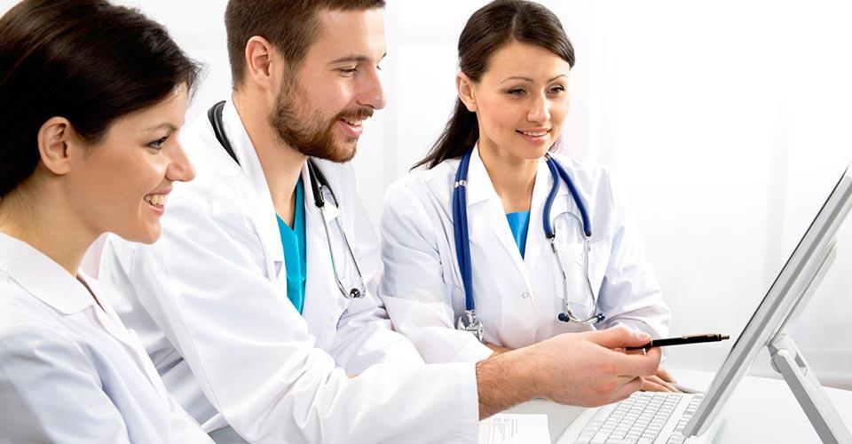 Trois soignants (deux femmes et un homme) en blouses blanches discutent devant un écran d'ordinateur