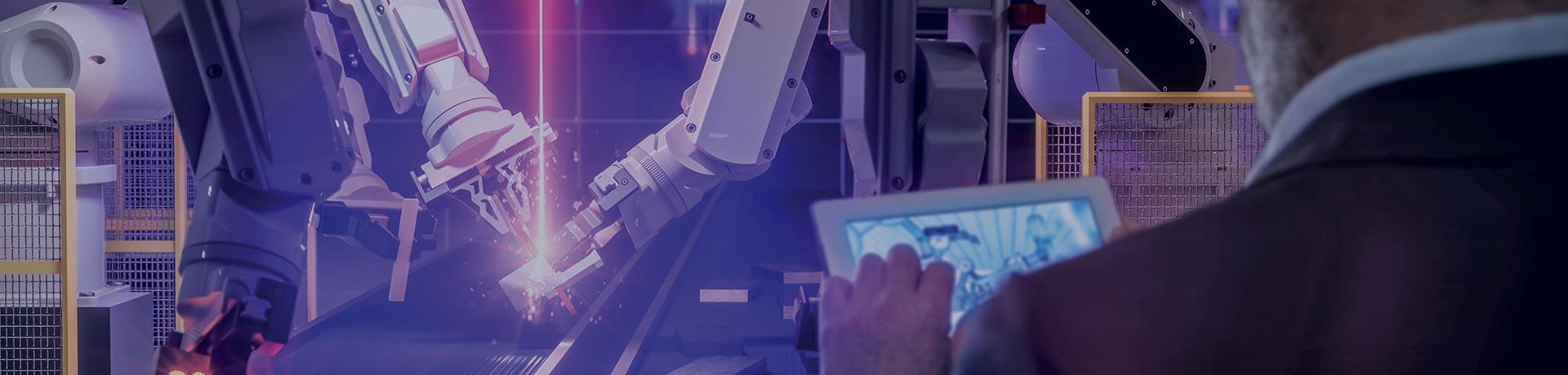 Un homme tient une tablette dans ses mains face à des bras robots