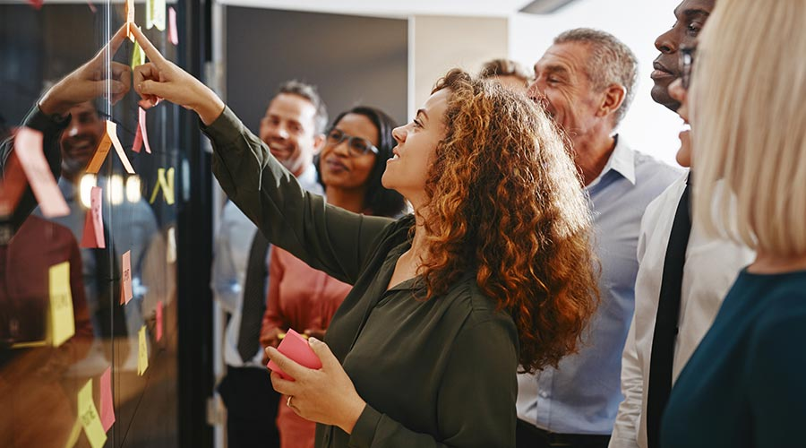 Une groupe de personnes en train de coller des postits sur un tableau