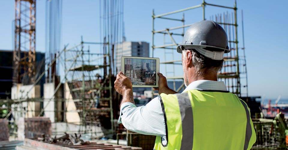 A man is standing in front of a construction site. He holds a tablet in his hands.