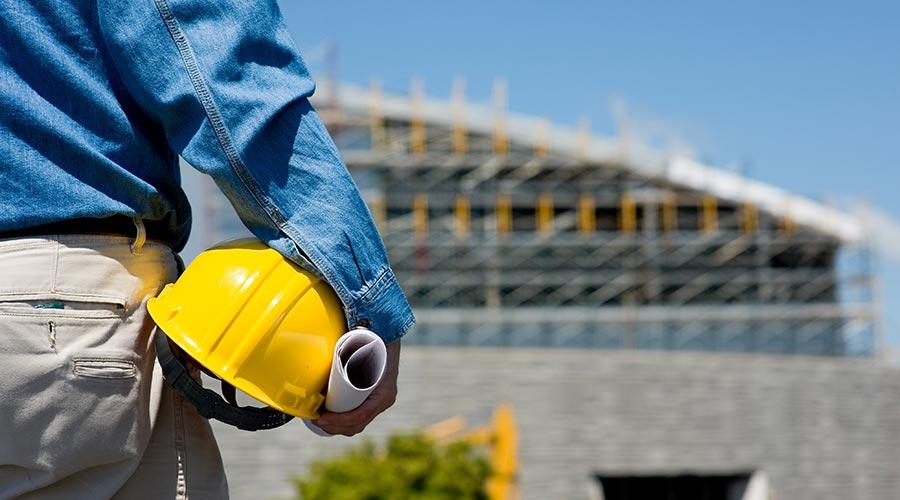 Un homme tient son casque jaune devant un chantier de construction
