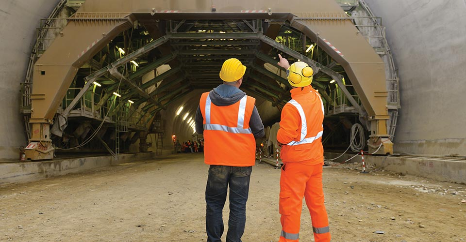 Two men in front of a tunnel construction