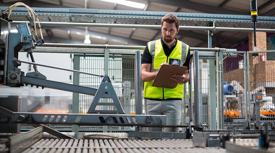 Un homme avec un gilet jaune en train de contrôler une ligne de production