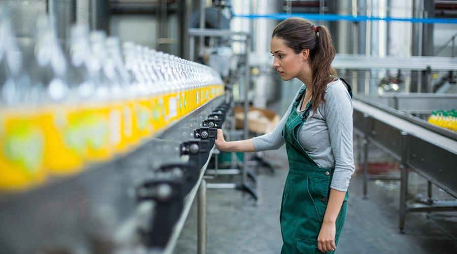 Une femme avec un tablier en train de contrôler une ligne de production