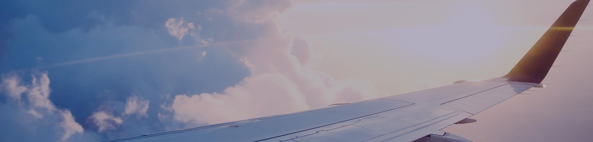 An aircraft wing in the sky with clouds in the background