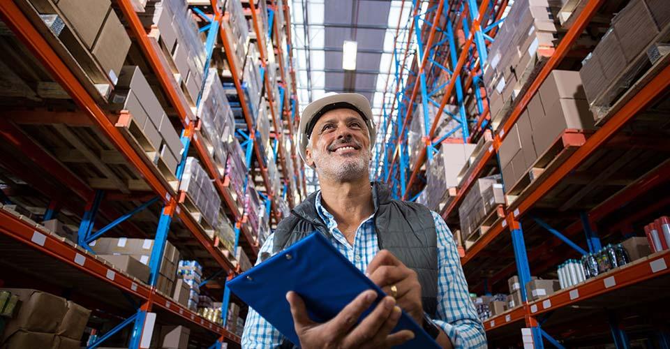 Un homme dans un entrepôt tient un porte document bleu dans ses mains