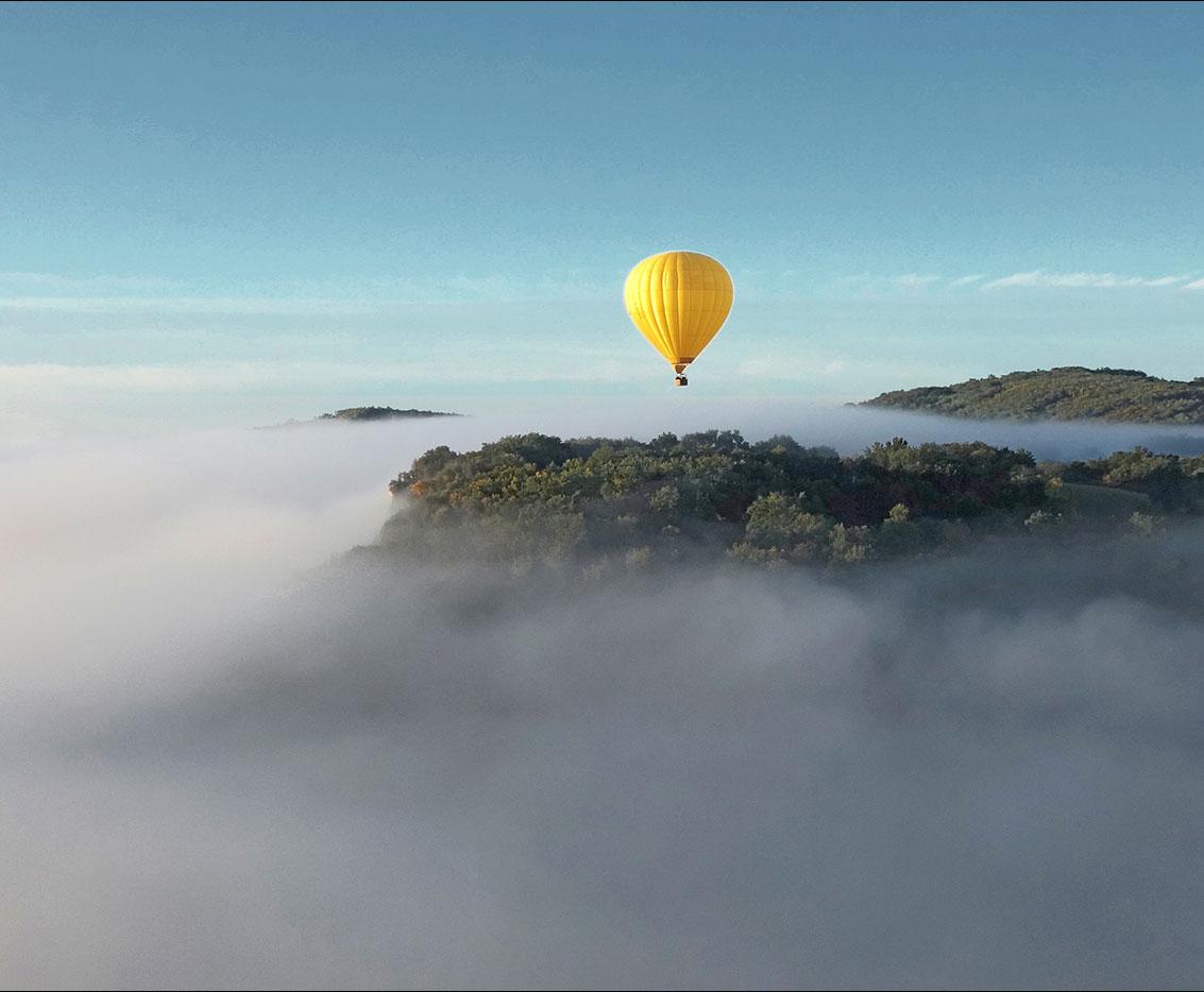 une montgolfière s'envole au dessus des montagnes
